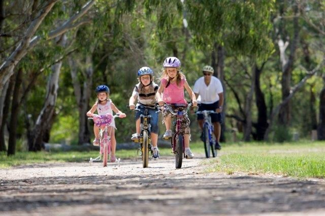 Three sisters varying in age riding their bikes through a trail, their father rides his back behind them